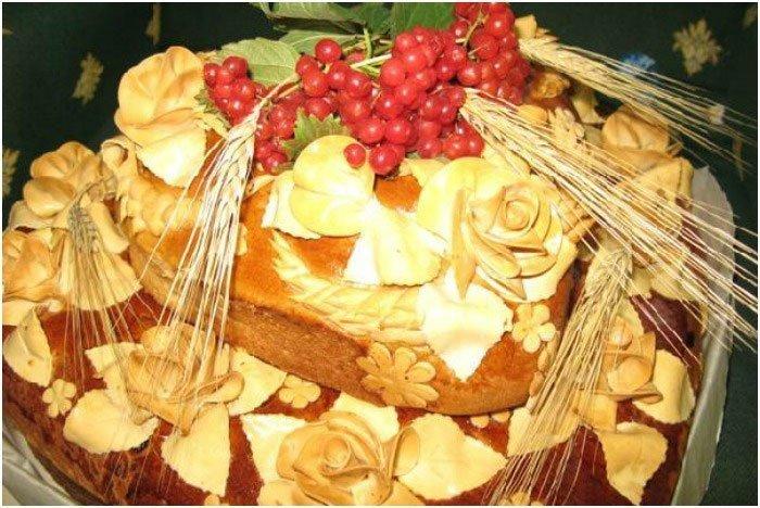 Каравай украшенный колосьями пшеницы и веткой с ягодами смородины.